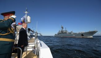 Russian President Vladimir Putin, second left, and Defence Minister Sergei Shoigu, left, arrive to attend the military parade during the Navy Day celebration in St.Petersburg, Russia, Sunday, July 26, 2020. (Alexei Druzhinin, Sputnik, Kremlin Pool Photo via AP)