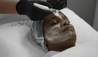 """A skin lightening mask is applied to the face during a demonstration for the Associated Press Tuesday, July 7, 2020, at the Skin and Body International Centre in Lenasia, Johannesburg. For years, cosmetics giants Unilever and L'Oreal have marketed skin whitening creams to women across the globe with less-than-subtle ads promoting """"fair skin"""" as more desirable than naturally darker shades. In the wake of mass protests against racial injustice in the U.S., these corporations are re-branding their skin lightening products in Africa, Asia and the Middle East, but for generations of women raised on their messaging, the new marketing is unlikely to reverse deeply rooted prejudices around """"colorism"""", the idea that fair skin is better than dark skin. (AP Photo/Denis Farrell)"""