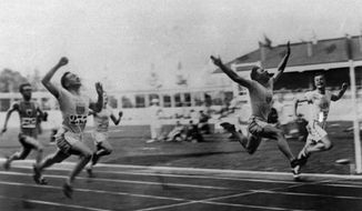 """FILE - In this 1920 file photo, Charles (Charley) Paddock, second from right, of the USA wins the 100 meters final with his famous """"flying finish"""" at the 1920 Summer Olympics in Antwerp, Belgium. Morris Kirksey, far right, of the USA was second, and Jackson Scholz of USA, left, was fourth. Third place Harry Edward not shown. (AP Photo/File)"""