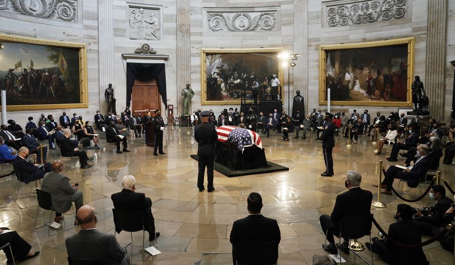 The flag-draped casket of the late Rep. John Lewis, D-Ga., a key figure in the civil rights movement and a 17-term congressman from Georgia, lies in state, Monday, July 27, 2020 at the Capitol in Washington,. (AP Photo/J. Scott Applewhite, Pool)