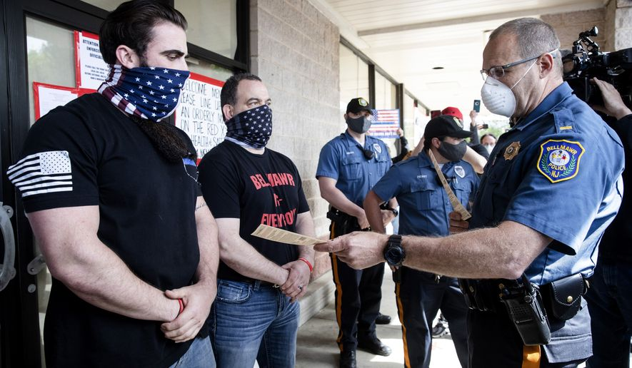 A police officer issues Atilis Gym co-owners Ian Smith, left, and Frank Trumbetti, center, summons outside their gym in Bellmawr, N.J., Tuesday, May 19, 2020. After repeatedly defying the governor's order to remain closed during the COVID-19 pandemic Smith and Trumbetti have been arrested on contempt charges. (AP Photo/Matt Rourke, File)
