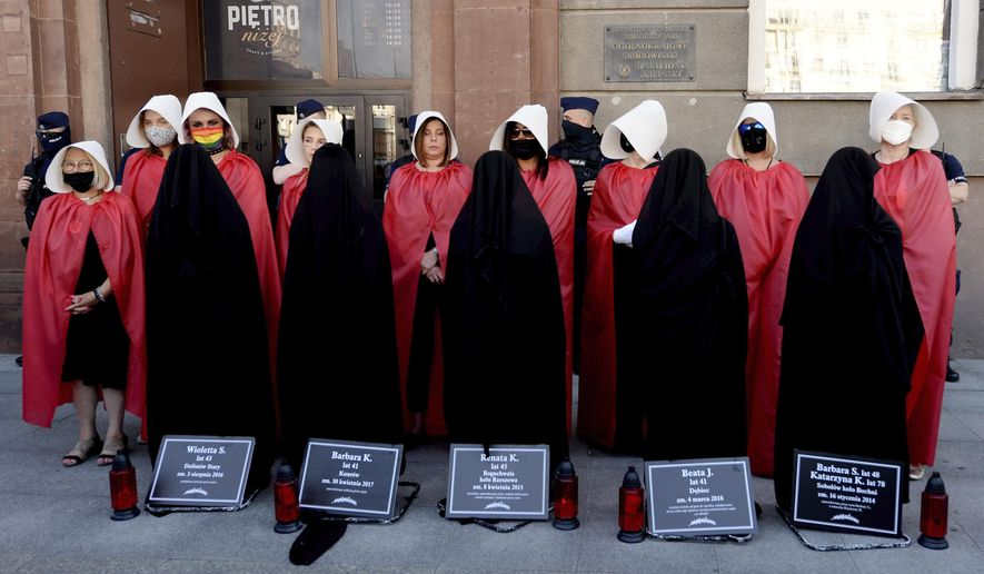 Members of Poland's women's rights organizations, with obituaries of women who fell victim to violence, protest against plans by the right-wing government to withdraw from Europe's Istanbul Convention on prevention of violence against women and children, in Warsaw, Poland, Friday,  July 24, 2020. (AP Photo/Czarek Sokolowski)