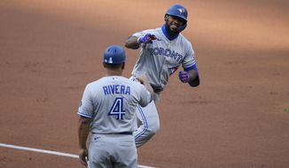 Toronto Blue Jays' Teoscar Hernandez, right, celebrates his home run with third base coach Luis Rivera (4) during the first inning of the team's baseball game against the Washington Nationals, Monday, July 27, 2020, in Washington. (AP Photo/Nick Wass)