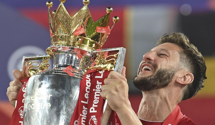 Liverpool's Adam Lallana celebrates with the trophy following the English Premier League soccer match between Liverpool and Chelsea at Anfield Stadium in Liverpool, England, Wednesday, July 22, 2020. Liverpool are champions of the EPL for the season 2019-2020. The trophy is presented at the teams last home game of the season. Liverpool won the match against Chelsea 5-3. (Paul Ellis, Pool via AP)