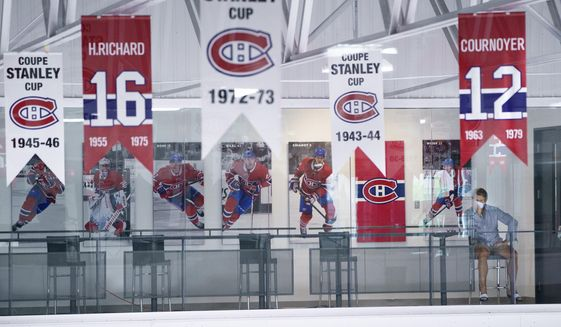 Montreal Canadiens general manager Marc Bergevin watches an NHL hockey practice at the team practice facility in Brossard, Quebec on Tuesday, July 21, 2020. (Paul Chiasson/The Canadian Press via AP)