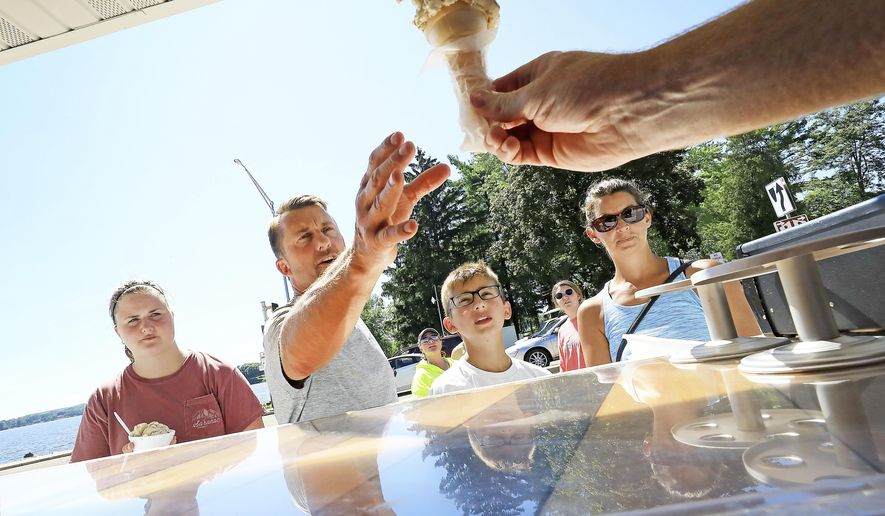 While waiting for the arrival of the Merrimac Ferry, visitors to the Merrimac Ferry Landing Concessions in Merrimac, Wis. receive treats from the business Thursday, July 16, 2020. (John Hart/Wisconsin State Journal via AP)
