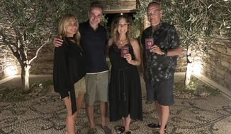 In this photo provided by Greek Prime Minister's Office, Greek Prime Minister Kyriakos Mitstotakis, second left, his wife Mareva Grabowski-Mitsotaki, left, pose next to U.S. actor Tom Hanks , right, and his wife Rita Wilson holding up their new Greek passports, in the island of Antiparos, Greece on Saturday, July 25, 2020. Greece offered citizenship Hanks, Wilson, and their two children, in recognition of the family's help in assisting victims of a deadly wildfire near Athens in 2018. (Greek Prime Minister's Office via AP)