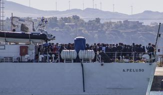 Migrants arrive in Porto Empedocle, Sicily, aboard two military ships after being transferred from the island of Lampedusa, where a number of small boat carrying migrants arrived in the last days, Monday, July 27, 2020. (Fabio Peonia/LaPresse via AP)