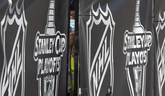 """A security guard peers out from behind NHL-branded fencing at the entrance where players arrive at Toronto's Royal York hotel, which is acting as the """"bubble"""" ahead of the return of the league's season following disruption due to the COVID-19 pandemic, Sunday, July 26, 2020. (Chris Young/The Canadian Press via AP)"""
