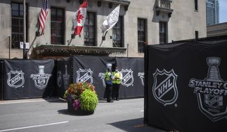 """Security guards stand by at a section of the street outside Toronto's Royal York hotel, which is closed off as NHL teams arrive at the """"bubble"""" ahead of the return of the league's season following a disruption due to the COVID-19 pandemic, in Toronto, Sunday, July 26, 2020. (Chris Young/The Canadian Press via AP)"""