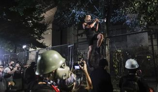 A demonstrator plays a trumpet from atop a steel fence during a Black Lives Matter protest at the Mark O. Hatfield United States Courthouse Sunday, July 26, 2020, in Portland, Ore. (AP Photo/Marcio Jose Sanchez)