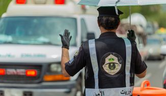 In this July 26, 2020 photo, a Saudi security officer motions to an ambulance at a checkpoint in the Mecca region ahead of the annual hajj pilgrimage. The Islamic pilgrimage has been dramatically downsized this year with only a few thousand residents of Saudi Arabia permitted to take part due to concerns over the coronavirus. (Saudi Ministry of Media)