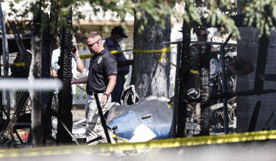 Police officers investigate a plane crash near Old Bingham Highway in West Jordan, Utah, on Saturday, July 25, 2020. (Yukai Peng/The Deseret News via AP)