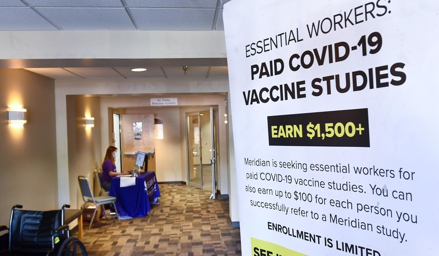 In this file photo, a poster is displayed in the entrance way looking for volunteers as the world's biggest study of a possible COVID-19 vaccine, developed by the National Institutes of Health and Moderna Inc.,  gets underway Monday, July 27, 2020, in Binghamton, N.Y. In a separate front on the coronavirus pandemic, NIH will run a clinical test of manufactured antibodies, both on hospitalized and non-hospitalized COVID patients. (AP Photo/Hans Pennink)