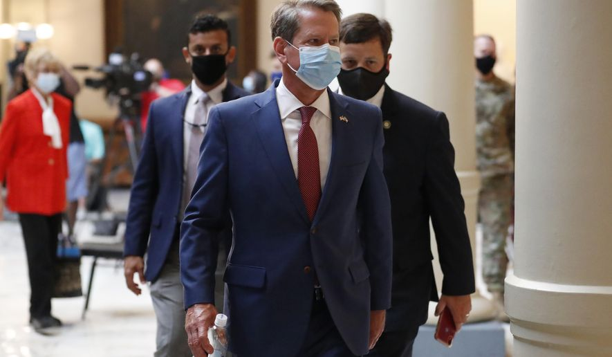 FILE - In this July 17, 2020, file photo, Georgia Gov. Brian Kemp returns to his office after giving a coronavirus briefing at the Capitol in Atlanta. Kemp says he's withdrawing a request for an emergency order that would block Atlanta from ordering people to wear masks in public or imposing other restrictions related to the COVID-19 pandemic. (AP Photo/John Bazemore, File)