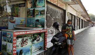 A man checks his mobile phone near rows of closed shops following months of lockdown due to the new coronavirus outbreak, in Bali, Indonesia on Monday, July 27, 2020. Indonesia has the highest number of coronavirus cases in Southeast Asia. (AP Photo/Firdia Lisnawati)