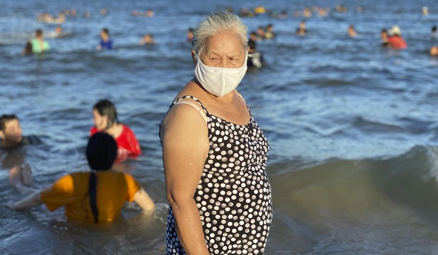 A woman wearing a face mask stands on a beach in Vung Tau city, Vietnam, Sunday, July 26, 2020. Vietnam on Sunday reimposed restrictions in one of its most popular beach destinations after a second person tested positive for the virus, the first locally transmitted cases in the country in over three months. (AP Photo/Hau Dinh)