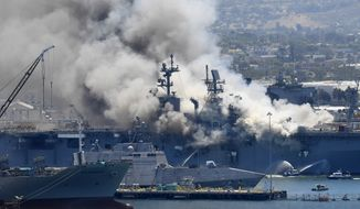 FILE - Smoke rises from the USS Bonhomme Richard at Naval Base San Diego Sunday, July 12, 2020, in San Diego after an explosion and fire Sunday on board the ship at Naval Base San Diego. Smoke from the fire that ravaged a Navy warship in San Diego Bay contained elevated levels of toxins, but air-quality authorities said area residents had little to fear. The San Diego County Air Pollution Control District found that smoke from the USS Bonhomme Richard contained a dozen potentially harmful substances, such as benzene chloromethane and acetonitrile, the San Diego Union-Tribune Reported. (AP Photo/Denis Poroy, File)