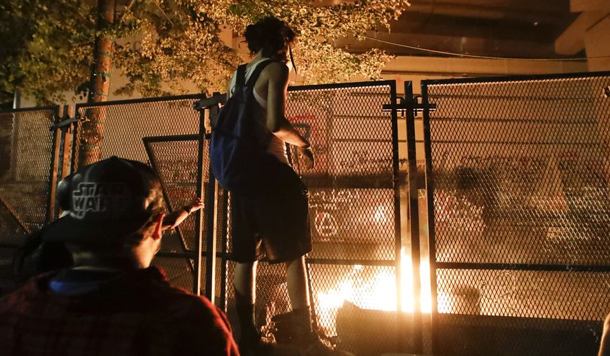 Demonstrators light a fire during a Black Lives Matter protest at the Mark O. Hatfield United States Courthouse Monday, July 27, 2020, in Portland, Ore. (AP Photo/Marcio Jose Sanchez)