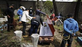 Relatives say goodbye to a 63-year-old man who died from a heart attack, which his family said was unrelated to COVID-19, at Xilotepec Cemetery in Xochimilco, Mexico City, Monday, July 27, 2020. (AP Photo/Rebecca Blackwell)