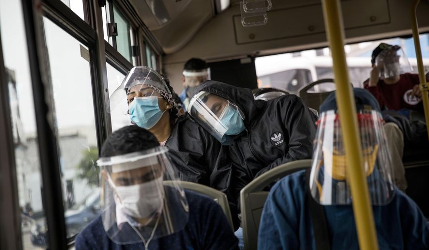 Commuters wearing protective face masks and face shields travel on a public bus in Lima, Peru, Wednesday, July 22, 2020. Peru ordered the mandatory wearing of protective face masks and shields on public transportation amid the new coronavirus pandemic. (AP Photo/Rodrigo Abd)