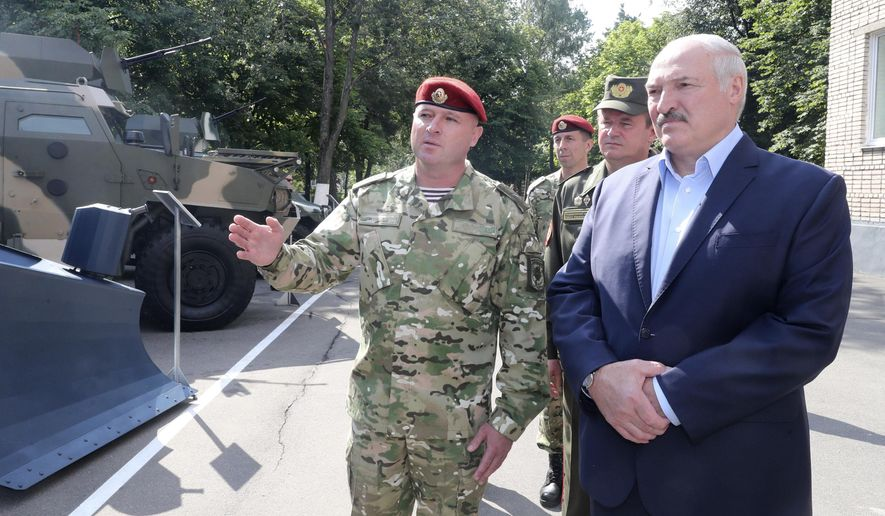 Belarus President Alexander Lukashenko, right, inspects police vehicles as he visits the Belarusian Interior Ministry special forces base in Minsk, Belarus, Tuesday, July 28, 2020. The presidential election in Belarus is scheduled for Aug. 9, 2020. (Nikolai Petrov/BelTA Pool Photo via AP)