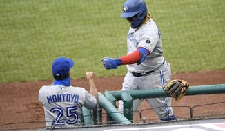 Toronto Blue Jays' Vladimir Guerrero Jr., right, celebrates his home run with manager Charlie Montoyo (25) during the second inning of a baseball game against the Washington Nationals, Tuesday, July 28, 2020, in Washington. (AP Photo/Nick Wass)