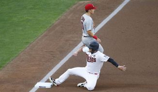 Minnesota Twins' Josh Donaldson advances safely to third past St. Louis Cardinals third baseman Tommy Edman on a first inning error in a baseball game Tuesday, July 28, 2020 in Minneapolis. (AP Photo/Jim Mone)