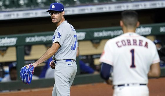 Los Angeles Dodgers relief pitcher Joe Kelly (17) looks back at Houston Astros' Carlos Correa (1) after the sixth inning of a baseball game Tuesday, July 28, 2020, in Houston. Both benches emptied during the exchange. (AP Photo/David J. Phillip) ** FILE **