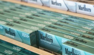 FILE - This Nov. 25, 2019 photo shows IQOS heated cigarette heatsticks  displayed in an IQOS store in Richmond, Va.  Altria said Tuesday, July 28, 2020, that cigarette sales continue to decline as it pushes to expand sales of an alternative heated-tobacco product. The tobacco giant's second-quarter profit fell slightly but still beat Wall Street expectations when adjusted for one-time expenses. (AP Photo/Steve Helber, File)