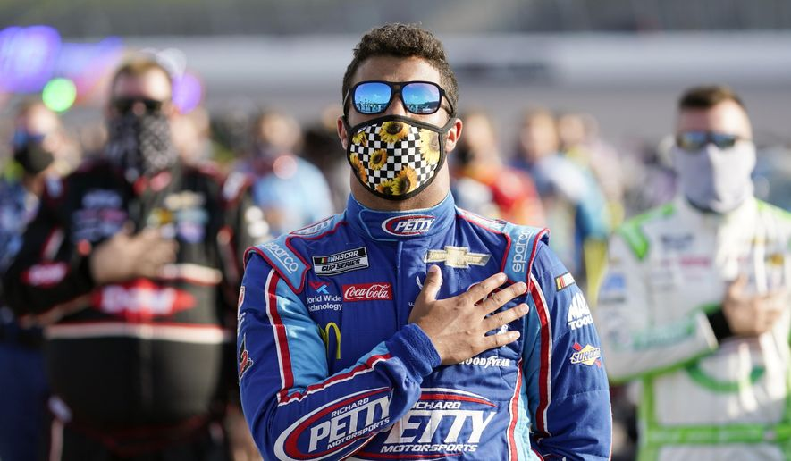 Driver Bubba Wallace, center, stands for the national anthem before a NASCAR Cup Series auto race at Kansas Speedway in Kansas City, Kan., Thursday, July 23, 2020. (AP Photo/Charlie Riedel)