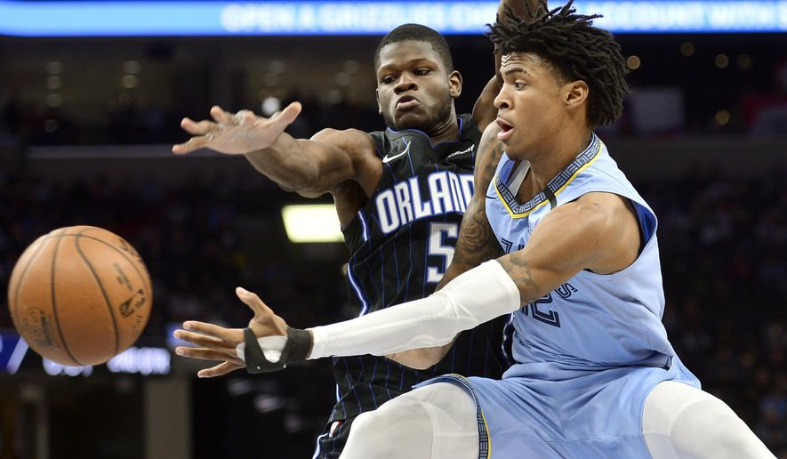 FILE - In this March 10, 2020, file photo, Memphis Grizzlies guard Ja Morant, right, passes the ball as Orlando Magic center Mo Bamba (5) defends during the first half of an NBA basketball game in Memphis, Tenn. Forget dealing with a rookie wall or stumbling into the playoffs exhausted and banged-up. The NBA's break for the coronavirus pandemic gave rookies an offseason within a season. They have had the chance to heal up, study lots of film and gain some much-needed pounds to better handle the grueling season in a league filled with savvy veterans. (AP Photo/Brandon Dill, File)