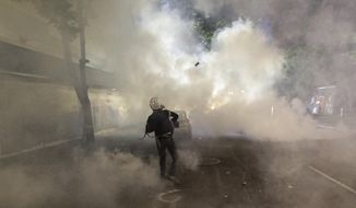 A demonstrator throws a tear gas canister back at federal officers during a Black Lives Matter protest at the Mark O. Hatfield United States Courthouse Tuesday, July 28, 2020, in Portland, Ore. (AP Photo/Marcio Jose Sanchez)