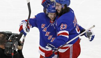 FILE - In this March 5, 2020, file photo, New York Rangers left wing Artemi Panarin and center Mika Zibanejad (93) celebrate after Zibanejad scored in overtime of the team's NHL hockey game against the Washington Capitals in New York. The Carolina Hurricanes are determined to make a second straight deep run in the Stanley Cup playoffs. That can only happen if they do something they have rarely done over the past decade: defeat the Rangers. (AP Photo/Kathy Willens, File)