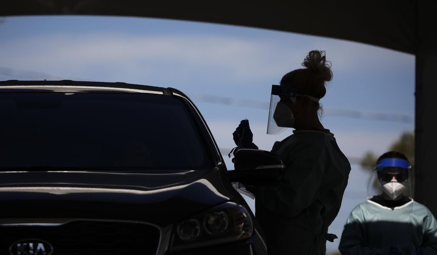 In this July 10, 2020, file photo health care workers test patients in their cars at a drive-thru coronavirus testing site in Las Vegas. (AP Photo/John Locher, File)