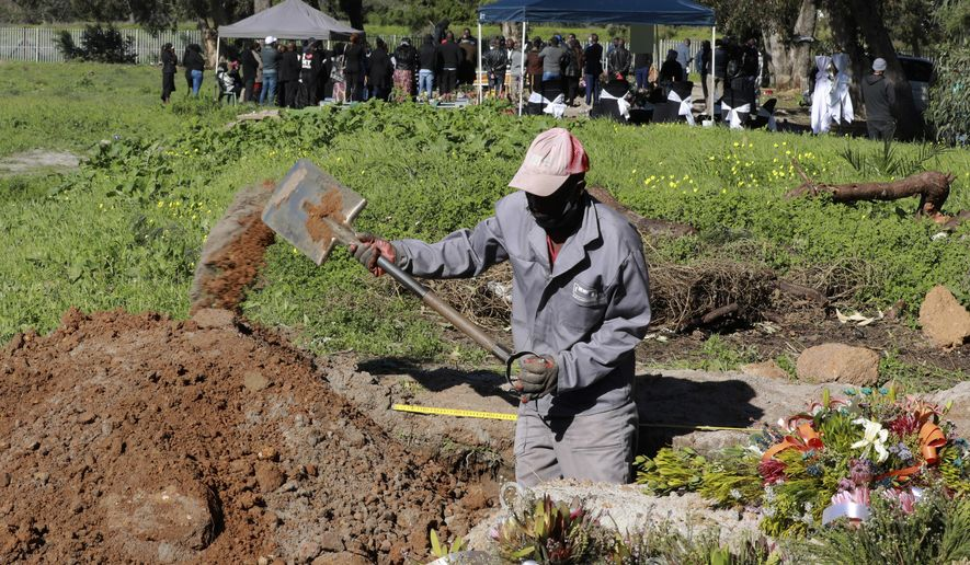 FILE - In this July 15, 2020, file photo, a grave digger prepares graves in the COVID-19 section of the Maitland Cemetary in Cape Town, South Africa as a burial takes place in the background. For months, the city of Cape Town was the biggest coronavirus hot spot in Africa. Now, finally, there are signs of relief. (AP Photo/Nardus Engelbrecht, File)