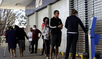 An employee of the state-run bank Caixa Economica, right, gives customers a ticket number before they wait in line at a nearby bank entrance in Brasilia, Brazil, Thursday, July 23, 2020. People are trying to get access to $ 150 dollars of government aid for the unemployed and independent workers affected by the COVID-19 pandemic lockdown. (AP Photo/Eraldo Peres)