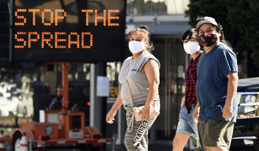 Pedestrians wear masks as they walk in front of a sign reminding the public to take steps to stop the spread of coronavirus, Thursday, July 23, 2020, in Glendale, Calif. Three out of four Americans, including a majority of Republicans, favor requiring people to wear face coverings while outside their homes, a new poll finds, reflecting fresh alarm over spiking coronavirus cases and a growing embrace of government advice intended to safeguard public health. (AP Photo/Chris Pizzello)