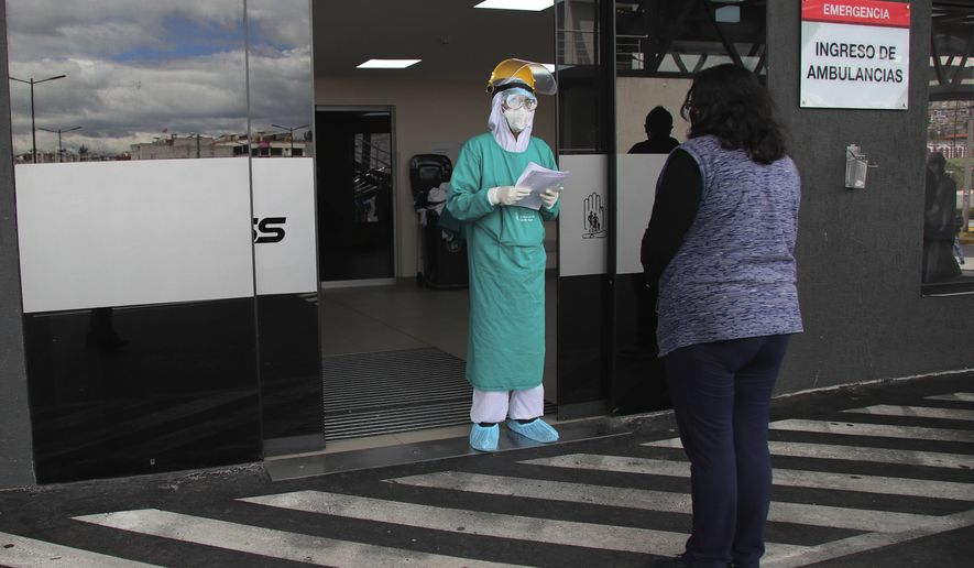 A doctor informs a woman about the condition of her relative who was admitted with COVID-19 to the Seguridad Social hospital in Quito, Ecuador, Monday, July 27, 2020. (AP Photo/Dolores Ochoa)