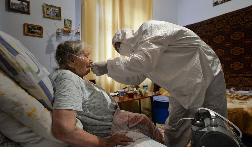 A volunteer in a protective suit and gloves sets an oxygen concentrator to help a suspected coronavirus patient breathe at her apartment in Bishkek, Kyrgyzstan, Friday, July 24, 2020. Volunteers have played a big role in dealing with a wave of coronavirus cases in Kyrgyzstan. Many started doing house calls to patients who couldn't get into a hospital, bringing oxygen concentrators with them. (AP Photo/Vladimir Voronin)