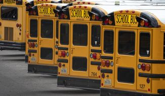 Fairfax County Public School buses are lined up at a maintenance facility in Lorton, Va., Friday, July 24, 2020. The nation's 10th largest school district plans an all-virtual start to the fall semester amid the Covid-19 pandemic. (AP Photo/J. Scott Applewhite) ** FILE **
