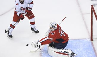 Washington Capitals goaltender Braden Holtby (70) makes a save against Carolina Hurricanes center Vincent Trocheck (16) during the first period of an exhibition NHL hockey game Wednesday, July 29, 2020 in Toronto. (Nathan Denette/The Canadian Press via AP) ** FILE **