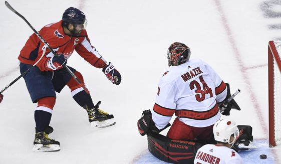 Washington Capitals left wing Alex Ovechkin (8) scores past Carolina Hurricanes goaltender Petr Mrazek (34) during the second period of an exhibition NHL hockey game Wednesday, July 29, 2020 in Toronto. (Nathan Denette/The Canadian Press via AP)