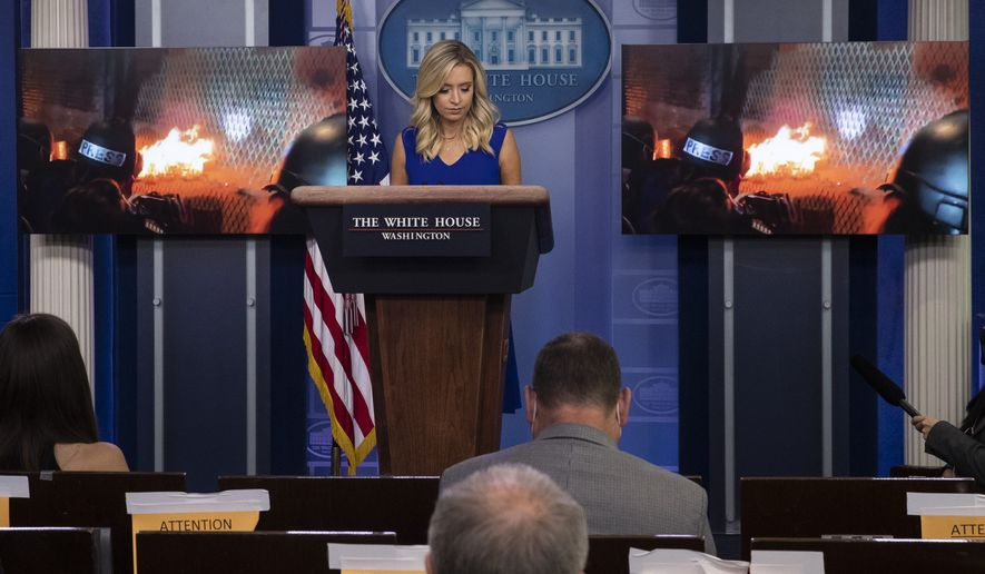 FILE - In this July 24, 2020, file photo White House press secretary Kayleigh McEnany stands as a video from Portland, Ore., is shown during a press briefing in the James Brady Press Briefing Room at the White House in Washington. Trump is painting a dystopian portrait of what Joe Bidens America might look like, asserting crime and chaos would ravage communities should the former vice president win the White House in November. Left unmentioned by Trump is that a recent surge in violent crime recently endured in several big American cities has come under his watch. (AP Photo/Alex Brandon, File)