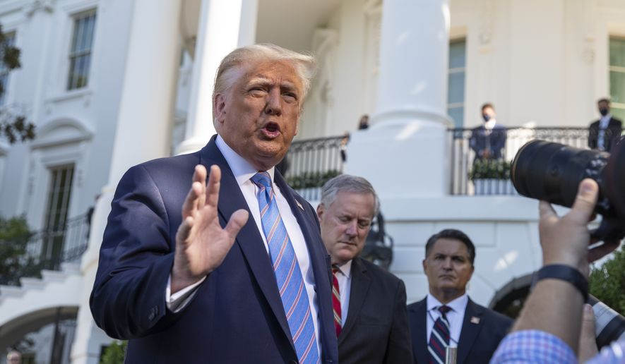 President Donald Trump, accompanied by White House Chief of Staff Mark Meadows, second from left, speaks with reporters as he walks to Marine One on the South Lawn of the White House, Wednesday, July 29, 2020, in Washington. Trump is en route to Texas. (AP Photo/Alex Brandon)