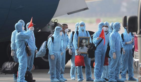 Vietnamese COVID-19 patients in protective gear, holding Vietnamese flags and carrying a portrait of the national leader Ho Chi Minh, arrive at the Noi Bai airport in Hanoi, Vietnam, on Wednesday, July 29, 2020. The 129 patients who were working in Equatorial Guinea are brought home in a repatriation flight for treatment of the coronavirus. (Tran Huy Hung/VNA via AP)