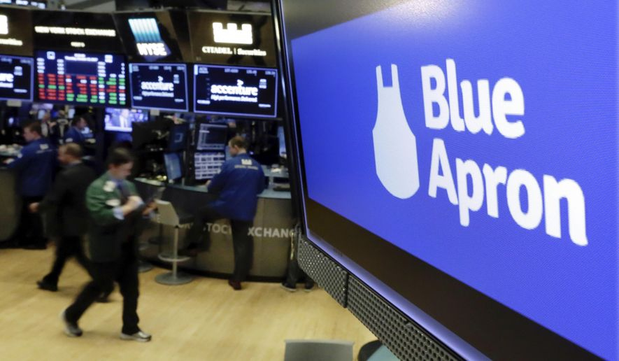 FILE - The logo for Blue Apron appears on a screen above the trading floor of the New York Stock Exchange, in this Thursday, Oct. 19, 2017, file photo. Scott's Miracle-Gro and Blue Apron are among the businesses seeing strong consumer demand for their products amid the virus outbreak.  (AP Photo/Richard Drew, File)