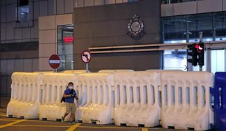 A journalist walks past the police headquarters in Hong Kong, Thursday, July 30, 2020. Hong Kong police have made their first major arrests under a new national security law, detaining four young people on suspicion of inciting secession. Police say they arrested three males and one female, aged 16 to 21, at three locations. All are believed to be students. (AP Photo/Kin Cheung) ** FILE **