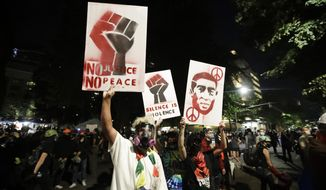 Demonstrators hold signs during a Black Lives Matter protest at the Mark O. Hatfield United States Courthouse Monday, July 27, 2020, in Portland, Ore. (AP Photo/Marcio Jose Sanchez)