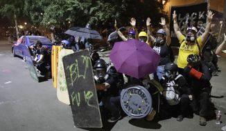 """EDS NOTE: OBSCENITY - Demonstrators, including members of the """"Wall of Moms,"""" top right, shield themselves from crowd control munitions and tear gas launched by federal officers during a Black Lives Matter protest at the Mark O. Hatfield United States Courthouse Wednesday, July 29, 2020, in Portland, Ore. (AP Photo/Marcio Jose Sanchez)"""